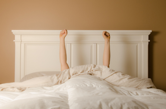Man in bed with arms raised in victory © sharpshutter22 | stock.adobe.com